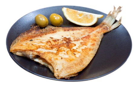 fried sole fish on black plate isolated on white background photo