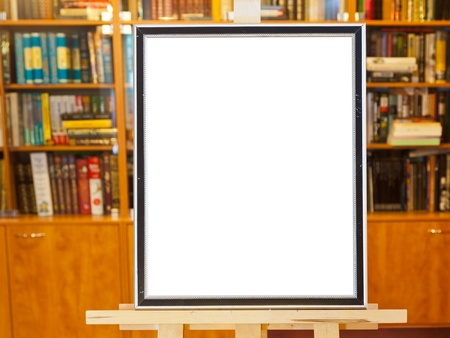 white canvas of picture frame on easel with clipping path and home library on background photo