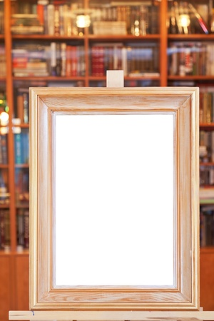 white canvas of wide picture frame on easel with clipping path and home library on background photo