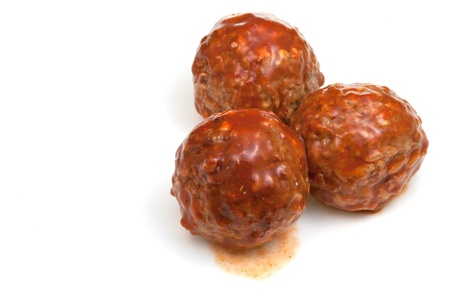 portion roasted meatballs under meat sauce on white plate photo