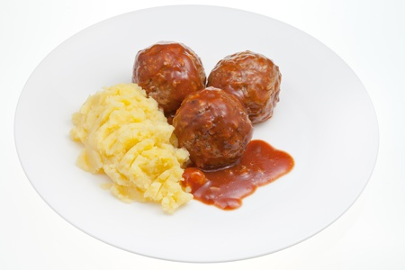 roasted meatballs under meat sauce and mashed potato on plate isolated on white background photo