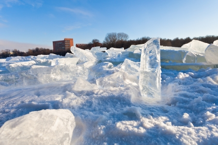 house and blocks of clear river ice in cold winter day in Moscow, Russia photo