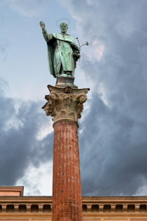catholicity: statue and column of Saint Dominic near Basilica of San Domenico with gray clouds, Bologna, Italy Stock Photo