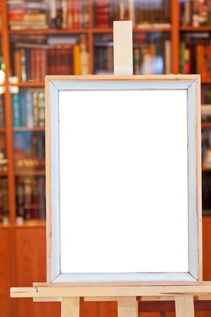 white canvas of simple picture frame on easel with clipping path and home library on background photo