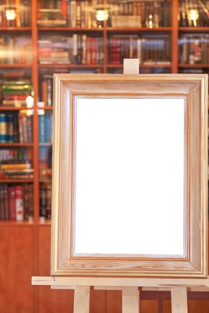 white canvas of wide picture frame on easel with clipping path and home library on background Stock Photo - 17166679