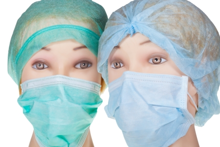 protective mask: two female mannequin doctor heads wearing textile surgical cap and medical protective mask isolated on white background