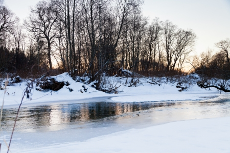 snow banks of forest river at winter sunset photo