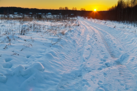 sunset under dark blue winter snowy country road photo