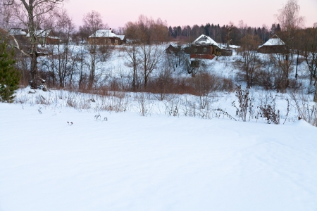 view of snow country houses at pink winter dusk photo