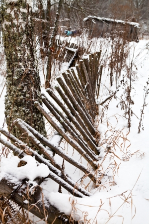 palisade: ramshackle wooden palisade in winter village Stock Photo