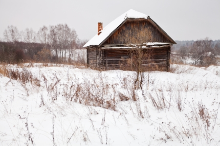 abandoned wooden house in snow-covered village in winter day photo