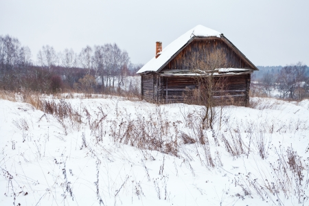 abandoned rustic house in snow-covered village in winter day photo