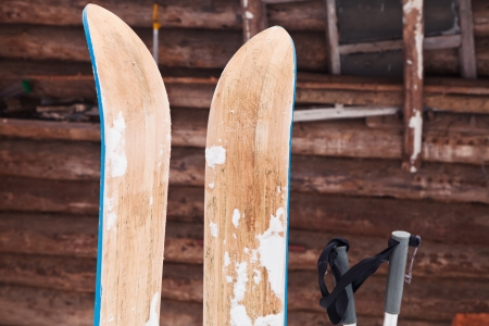 pair of wide wooden hunting skis and log house wall in winter day photo
