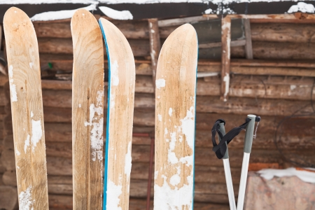 ski run: two pairs of wide skis and log house wall in winter day