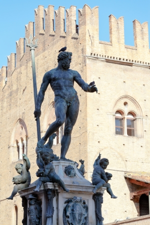 Fountain of Neptune on Piazza del Nettuno and Re Enzo palace in Bologna in sunny day, Italy