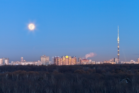 view of full moon under city in winter evening photo