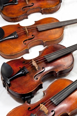 several used fiddles on white background close up stock photo