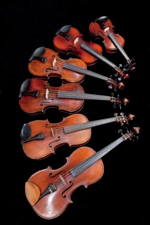 different sized violins on black background