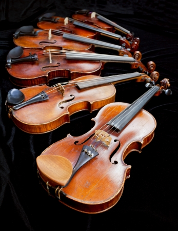 different sized violins with black background close up photo