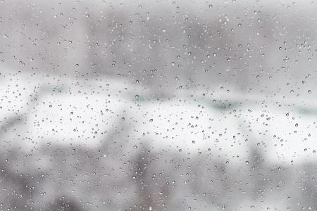 冬都市背景のガラス ウィンドウの雨滴