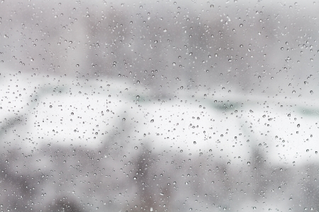 raindrops on glass window with winter urban background