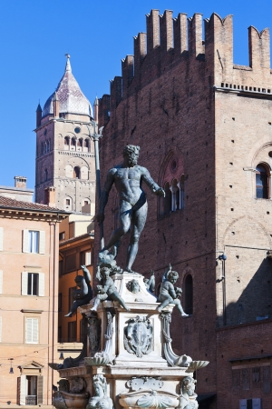 statue of Fountain of Neptune and wall of palazzo Re Enzo in Bologna in sunny day, Italy photo