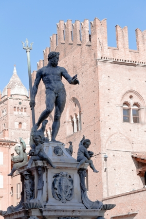 sculpture of Fountain of Neptune on Piazza del Nettuno and Re Enzo palace in Bologna in sunny day, Italy photo
