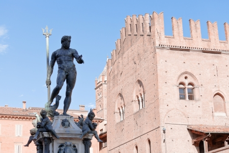 sculpture of Fountain of Neptune on Piazza del Nettuno and Re Enzo palace in Bologna in sunny day, Italy