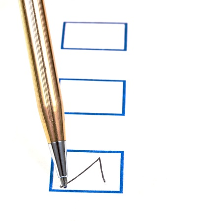 put tick in blue square box by metal gold ballpoint pen Stock Photo - 18215137