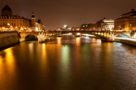 Seine river with pont notre dame and pont au change in Paris at night photo