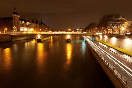 Panorama of Seine with quay and pont au change in Paris at night