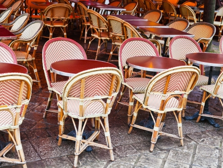 cane chairs and red table in paris outdoor cafe photo