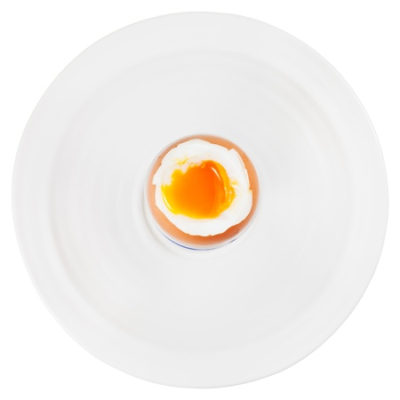 top view of soft boiled egg in egg cup on white plate isolated on white photo