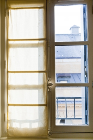 white textile drapes on sunny window in home photo