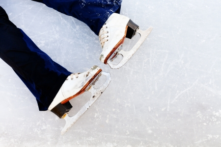 white leather skates on ice of outdoor open skating rink photo