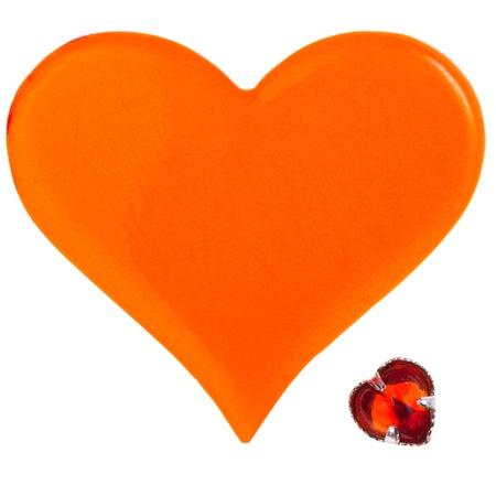 big orange plastic heart and small red glass heart isolated on white background photo