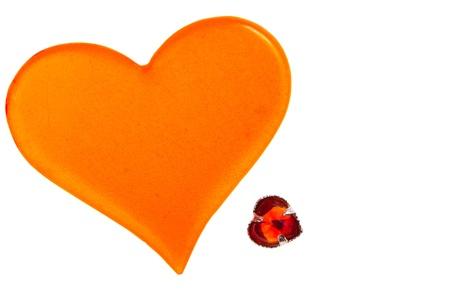 plastic heart: grande cuore di plastica arancione e piccolo cuore di vetro rosso isolato su sfondo bianco