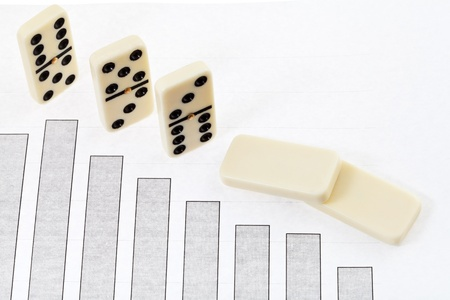 interdependence: business concept - fallen domino and graph of decline economy results