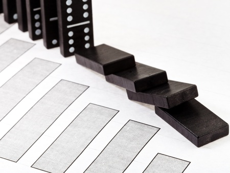 interdependence: business concept - fallen domino and falling economy diagram Stock Photo