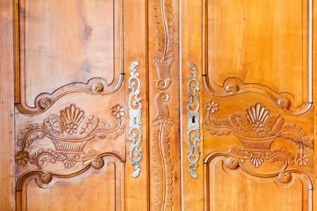 carved wooden door of old wardrobe photo