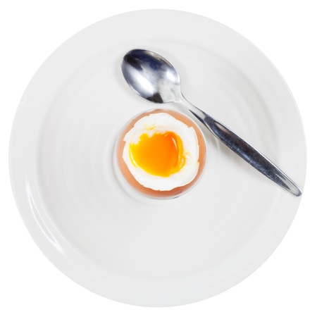 top view of soft boiled egg in egg cup and spoon on white plate isolated on white photo