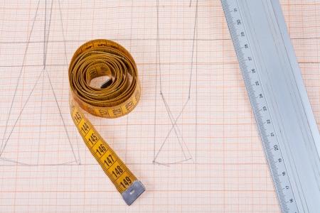yellow measure tape and metal ruler at graph paper photo