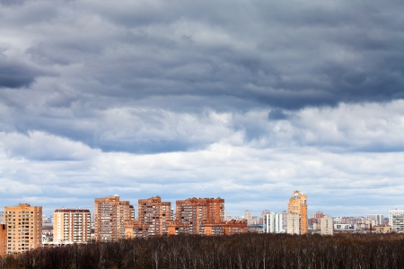 low grey rainy clouds under city in spring photo