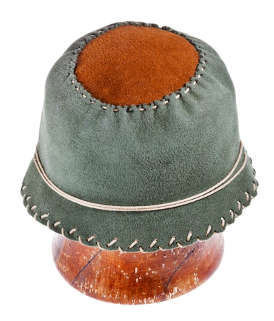 felt green soft cloche hat on wooden block isolated on white background photo