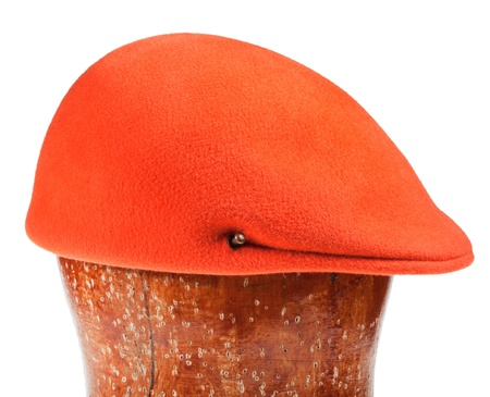 felt orange flat cap on wooden block isolated on white background Stock Photo - 19417859