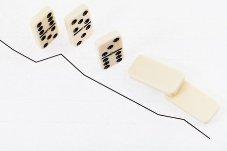 interdependence: business concept - fallen domino and graph of decline sales results