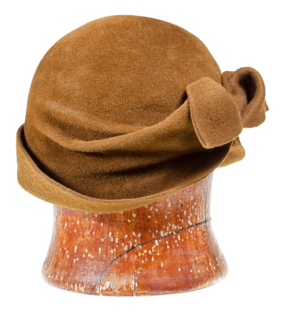 felt cloche hat decorated by bow on wooden block isolated on white background photo