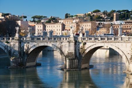view of historical city Rome through St Angel bridge on Tiber river photo