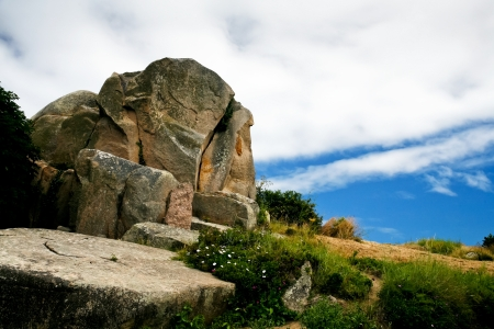 cotes d armor: granite block under blue sky and white cloud in Brittany, France Stock Photo