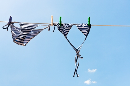 drying woman swimming suit with blue sky background